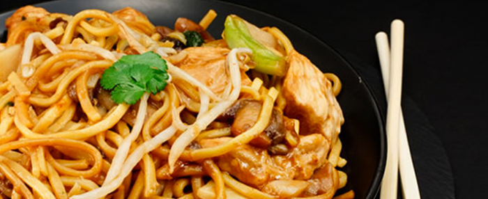 Plate of foodservice Amoy Asian Garlic Pork Lo Mein in a restaurant setting