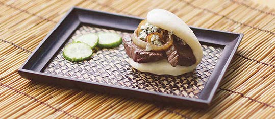 Plate of foodservice Amoy Asian Brasied Steak and Blue Cheese Bao in a restaurant setting