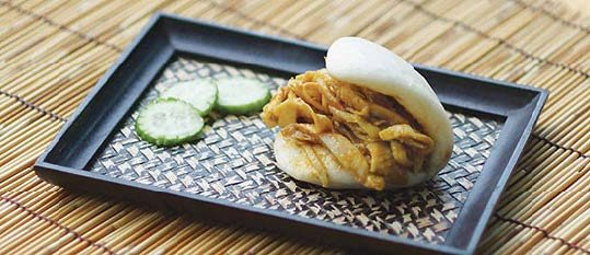 Plate of foodservice Amoy Asian Curry Chicken Salad Bao in a restaurant setting