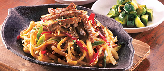 Plate of foodservice Amoy Asian Korean Style Spicy Stir-fry Udon in a restaurant setting