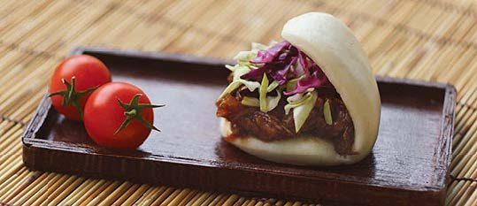 Plate of foodservice Amoy Asian Thai Grilled Chicken Satay Bao in a restaurant setting